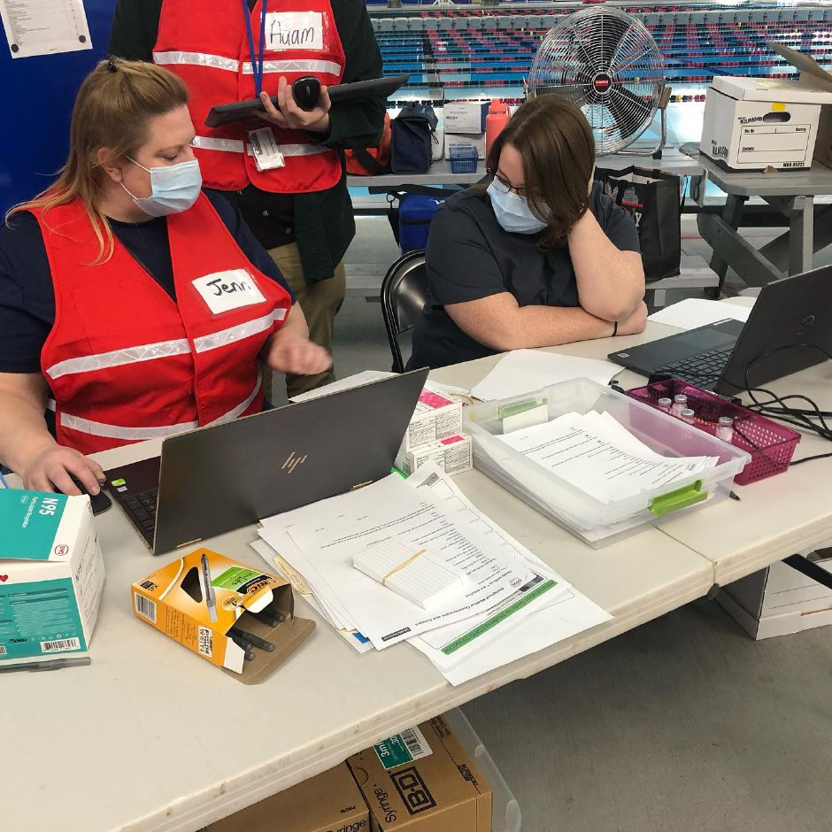 Photo courtesy of Chesprocott Health District – Volunteers at a recent Chesprocott Health District vaccine clinic, held at the Cheshire Community Pool, make sure all who attend are signed in.