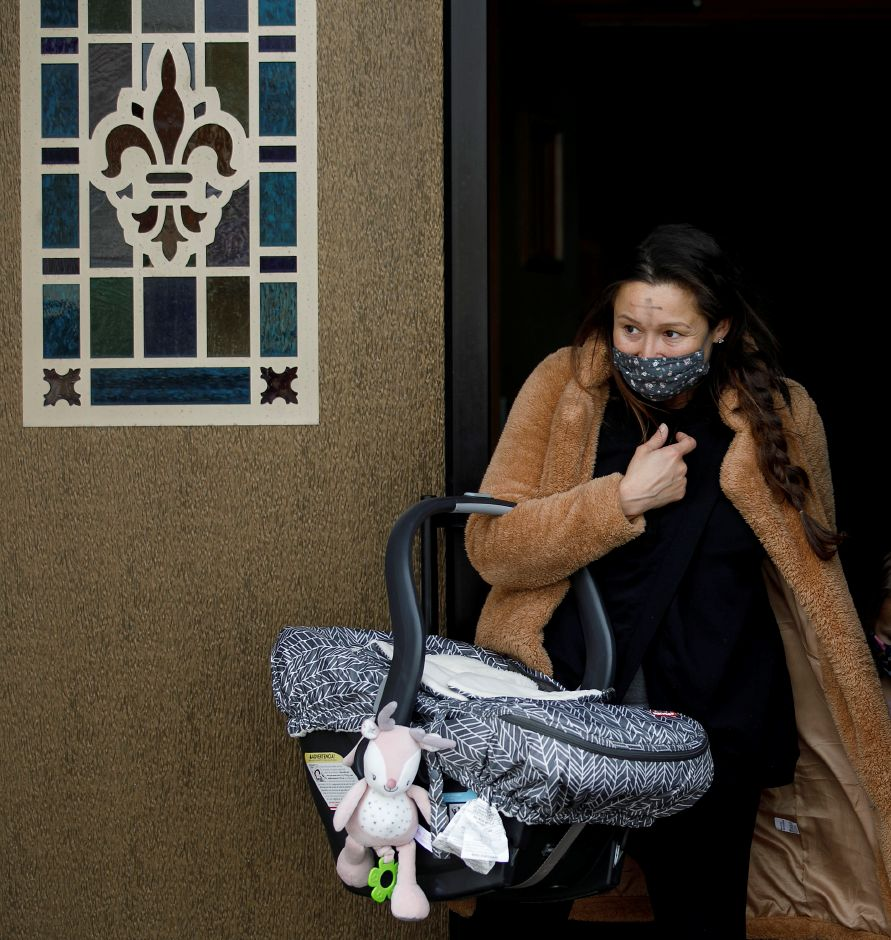Desirae Whittle, of Meriden, carries newborn daughter Willamina after receiving ashes on Ash Wednesday at Saint Bridget of Sweden Parish in Cheshire, Wed., Feb. 17, 2021.   Dave Zajac, Record-Journal