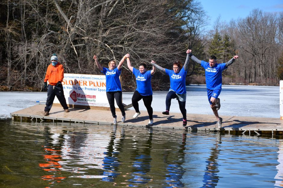 Team members hold hands on the way to jumping into the water during the 16th Sloper Plunge. Photo courtesy of Southington-Cheshire Community YMCA.