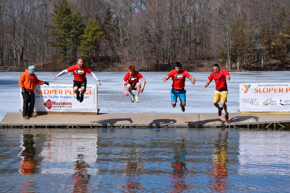 From left, Cheshire football head coach Don Drust, seniors Brad Krutz and Nick DiDomizio, and CHS Athletic Director Steve Trifone take to the air during the Sloper Plunge. Photo courtesy of Southington-Cheshire Community YMCA.
