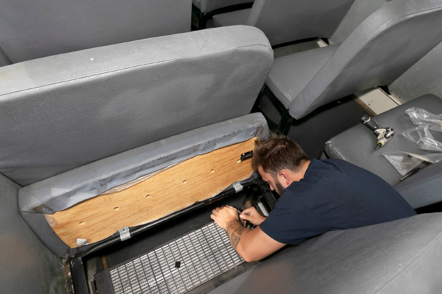 Mechanic Tyler Agostini replaces a heater filter under a seat cushion in a Meriden school bus at New Britain Transportation on the Berlin Turnpike in Meriden, Thurs., Aug. 27, 2020. Dave Zajac, Record-Journal