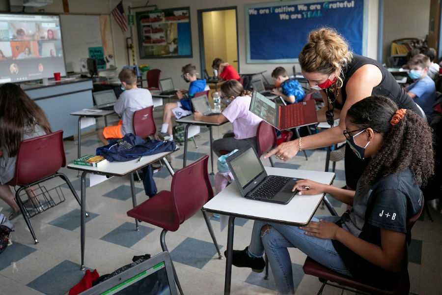 Distance learners are seen on a laptop held by teacher Kristen Giuliano who assists student Jane Wood, 11, in a seventh-grade social studies class at Dodd Middle School in Cheshire, Thurs., Sept. 24, 2020. Teachers in Cheshire have been adapting to new high technology classrooms that have been outfitted with cameras, microphones and speakers retrofitted into the ceilings and laptops that show all the students in their virtual classrooms. Dave Zajac, Record-Journal