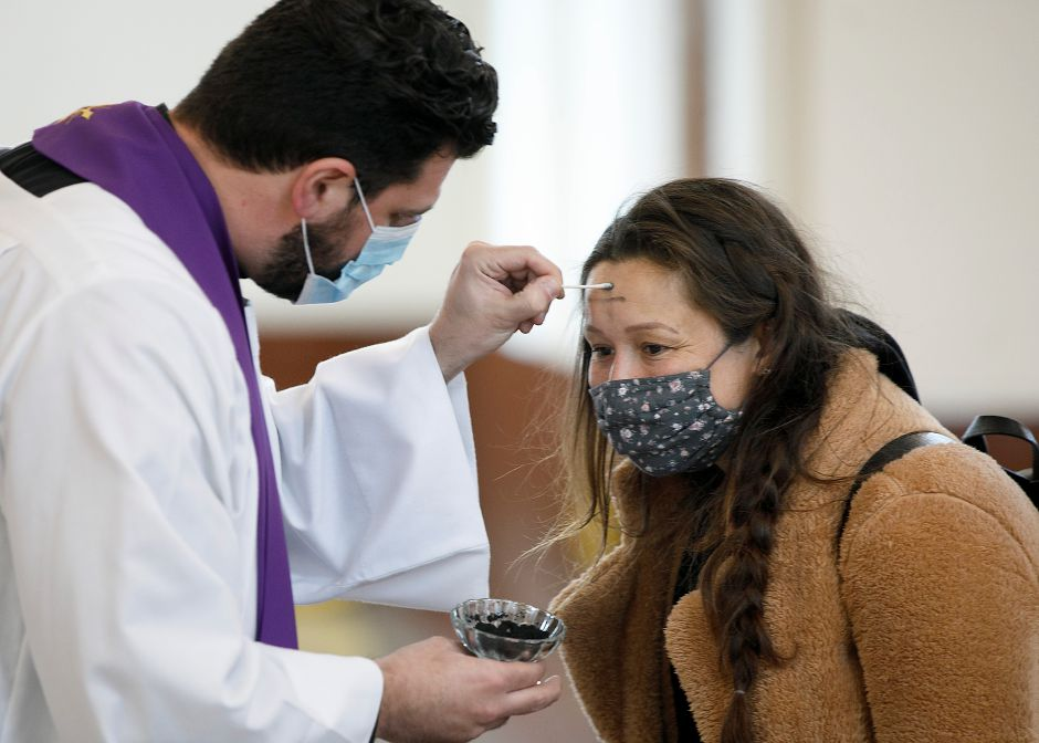 Rev. Anthony Federico makes a cross with a cotton swab while administering ashes to Desirae Whittle, of Meriden, on Ash Wednesday at Saint Bridget of Sweden Parish in Cheshire, Wed., Feb. 17, 2021. Dave Zajac, Record-Journal