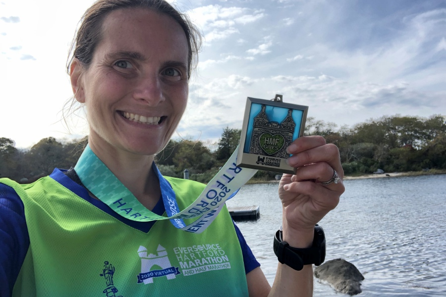 Sarah Redford holds up her medal from completing the Hartford Marathon Foundation's Grit & Gutsy 4 Challenge. From Oct. 8-11, she ran a 5K, a 10K, a half marathon, and a full marathon.