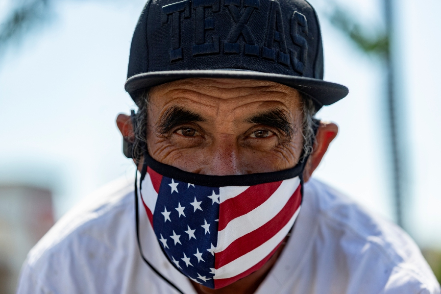 Street seller Jaime Caldera, originally from San Antonio, Texas, offers face masks for sale in Los Angeles Thursday, May 14, 2020. Leaving home in Los Angeles now requires bringing a face covering, part of the price for reopening more businesses and activities in America