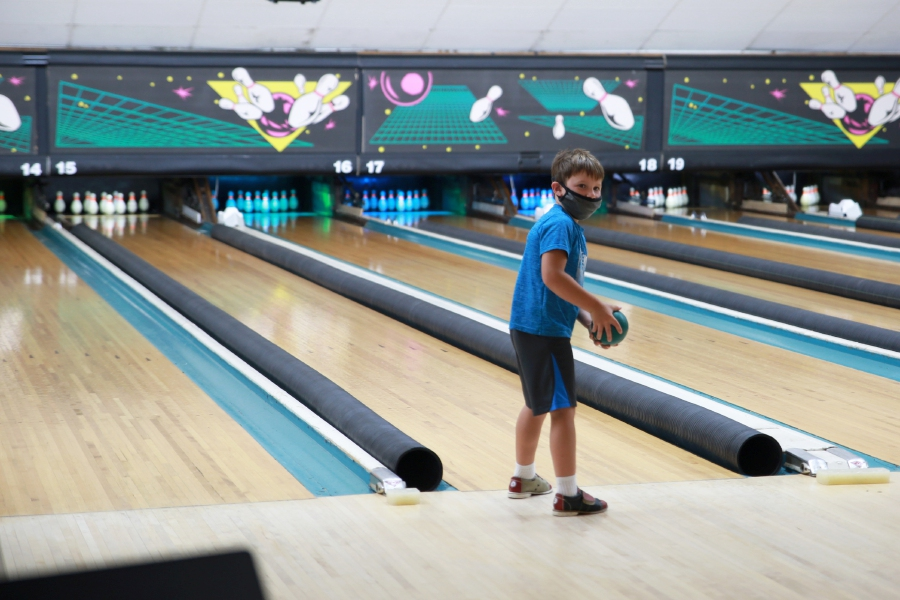 Stephen Johns (above) gets set to knock down a few pins, while several youngsters enjoy the popular arcade area (left) at the newly-updated Highland Bowl in Cheshire.