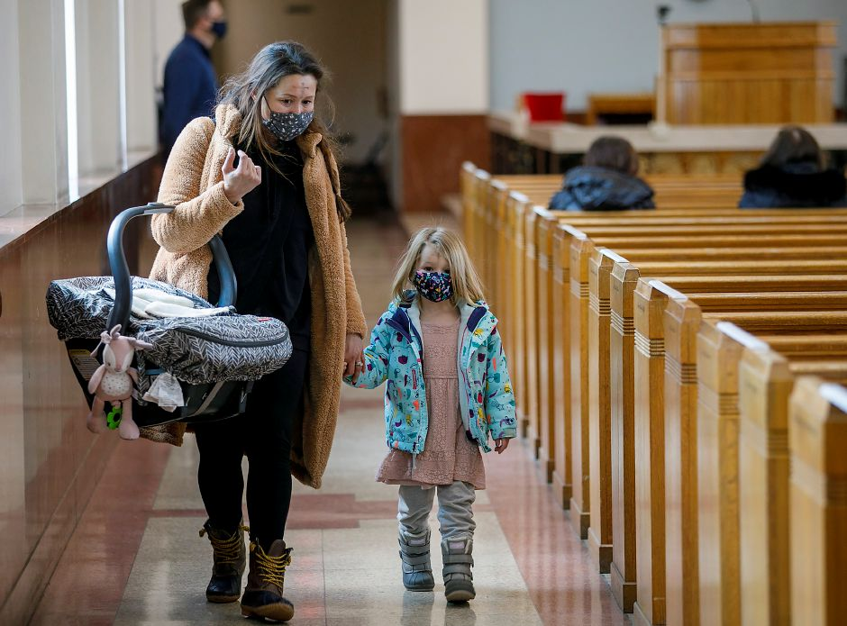 Desirae Whittle, of Meriden, carries newborn Willamina after receiving ashes with daughter Ingrid, 3, on Ash Wednesday at Saint Bridget of Sweden Parish in Cheshire, Wed., Feb. 17, 2021. Dave Zajac, Record-Journal