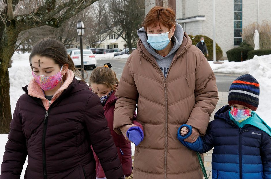 Kathleen Hodges, of Cheshire, and grandchildren, left to right, Brooke, 11, Nora, 7, and Scott, 7, walk a path outside Saint Bridget of Sweden Parish in Cheshire after receiving ashes on Ash Wednesday, Wed., Feb. 17, 2021. Dave Zajac, Record-Journal