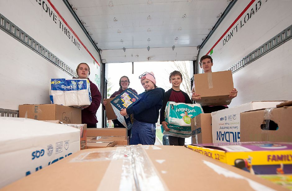 Al Valerio/Cheshire Herald -  Inside the trailer truck on the green, volunteers piled the boxed food and paper goods that were donated and then were transported to the Cheshire Food Pantry. Pictured from left to right are Brooke Smith, Micayla Nann, Bella Solimine, Levin Scassellati, and Rowan Scassellati.