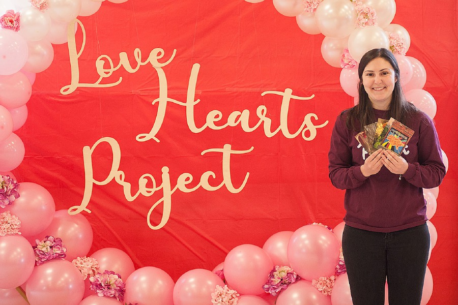 Alex Krohn holds up several of the postcards submitted as part of her Love Hearts Project.