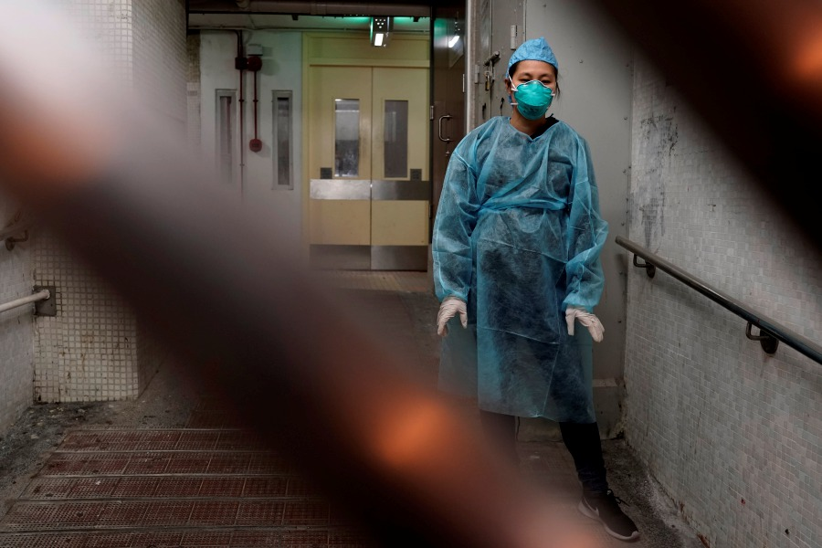 AP Photo/Kin Cheung – A personnel wearing protective suit waits near an entrance at the Cheung Hong Estate, a public housing estate during evacuation of residents in Hong Kong, Tuesday, Feb. 11, 2020. The Centre for Health Protection of the Department of Health evacuated some residents from the public housing estate after two cases of novel coronavirus infection to stop the potential risk of further spread of the virus.