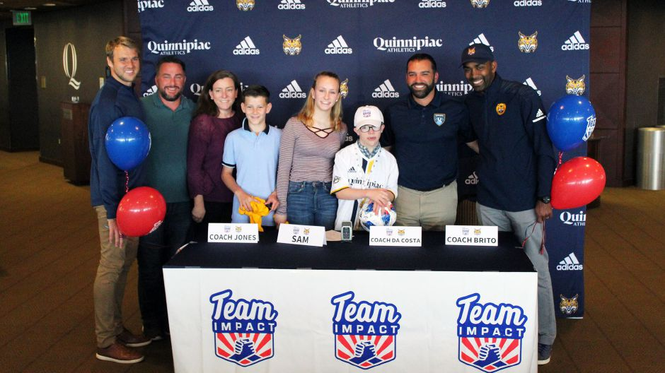 Submitted photo – Sam Hayden's signing day with QU Bobcats through Team IMPACT. Sam (middle) poses with his parents, Derek and Marcie Hayden (far left), his siblings, Molly and Luke (left), and his new Coaches; Coach Jones, Coach Da Costa, and Coach Brito (right) .