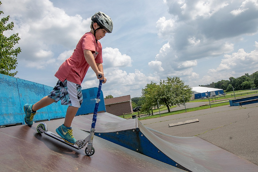 Dave Zajac/Record-Journal – Brendin Dorin Pierce, 8, scoots down a ramp at the skate park at Bartlem Park.