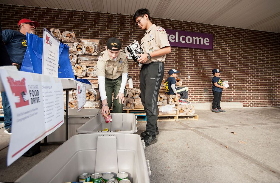 Al Valerio/Cheshire Herald - Boy Scout Troop 198 members Alex Michaud (left) and Austin Xu (right) put some canned goods donated by exiting shoppers into bins, to be taken to the Church Green for sorting and packing.
