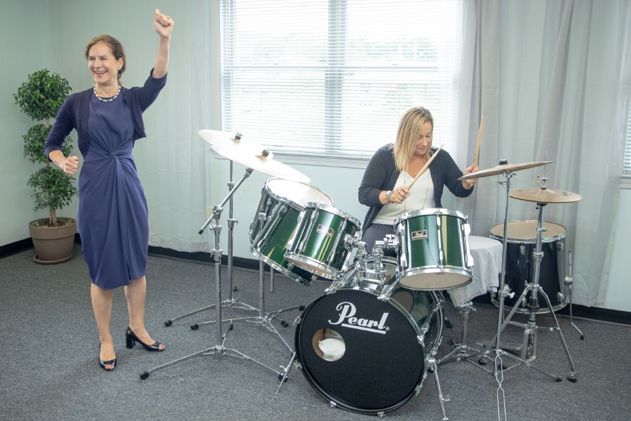 Devin Leith-Yessian/Record-Journal – State Rep. Liz Linehan, right, D-Cheshire, is cheered on by Lt. Gov. Susan Bysiewicz while playing the drums at the West Main Street Music Academy in Cheshire. The two toured businesses opening along West Main Street, centered around the renovation of the former Ball and Socket factory into an arts center of the same name.
