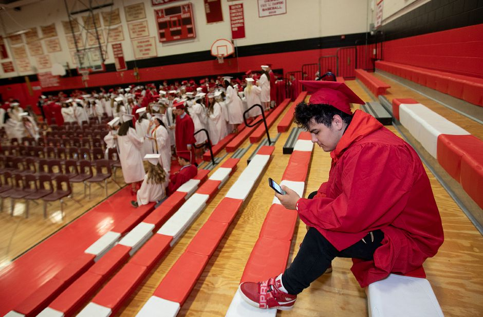 Graduate Dustin Ramos, 18, writes in a journal on his phone prior to graduation ceremonies at Cheshire High School, Thurs., June 13, 2019. Dave Zajac, Record-Journal