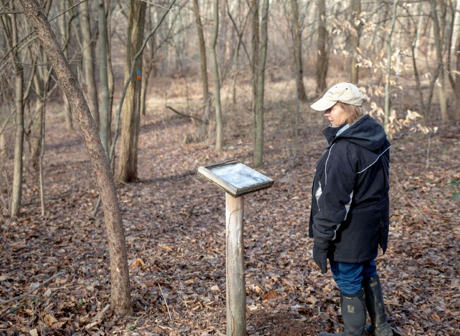 Devin Leith-Yessian/Record-Journal – Melinda Lazarus, of Cheshire, reads a sign along the trails through the Riverbound Farm Sanctuary. The Quinnipiac Valley Audubon Society and Cheshire Land Trust led a hike around the property for the First Day Hike on Jan. 1.