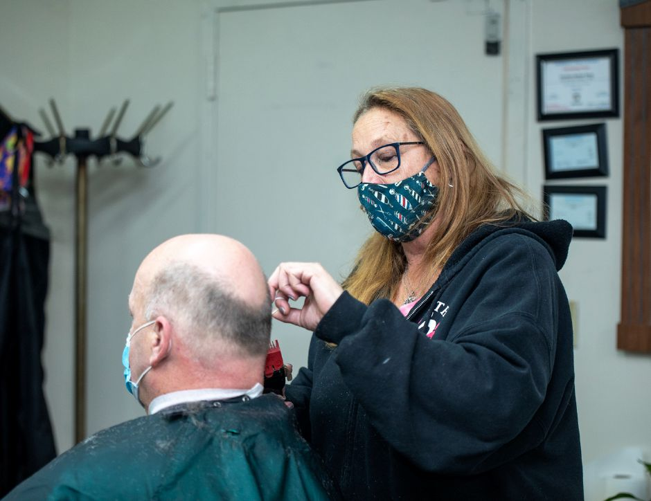 Maria Mazzacane Perez, of Cheshire, gives a customer a haircut at the Cheshire Barber Shop on Jan. 4, 2021. The business is celebrating 70 years in operation since Mazzacane