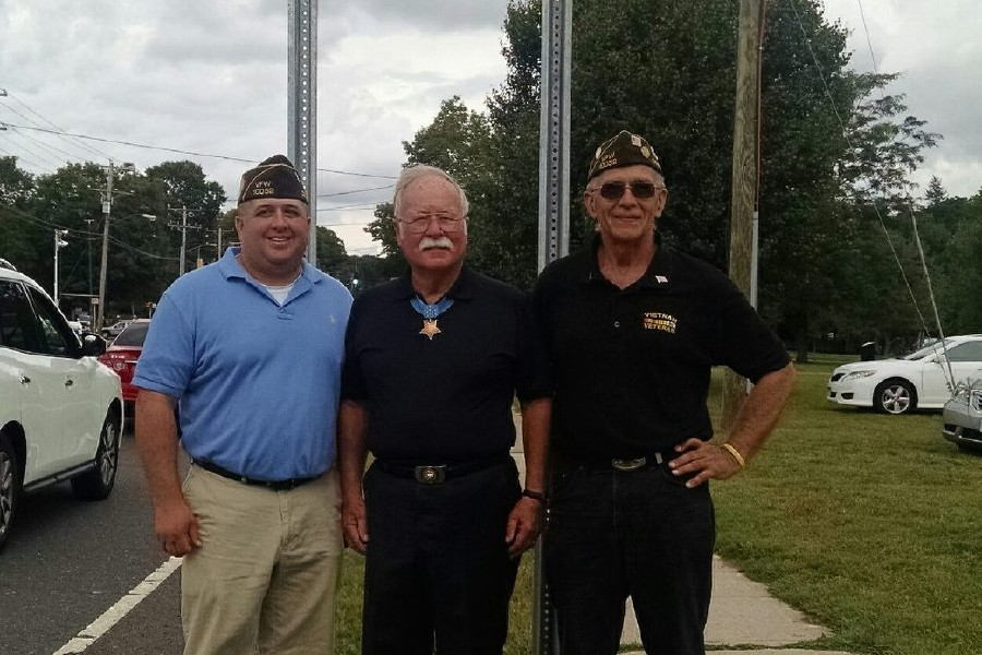 File photo – Jeff Falk (left) poses for a picture in front of the Medal of Honor Memorial Highway sign in Cheshire with Medal of Honor recipient and Cheshire native Harvey Barnum (center), as well as Falk's father, Don Falk, also a veteran.